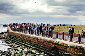 Hundreds of people visiting the Statue of Liberty.